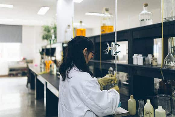 female worker using beakers and equipment on table in factory laboratory