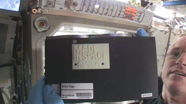 Astronaut Barry Wilmore shows off the first 3-D printed part in space inside the International Space Station.